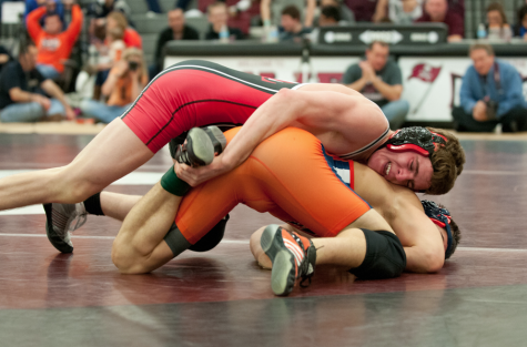 Alumni Aaron Otiker takes down his opponent in a 2013 wrestling match.