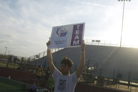 Senior Carter Benno proudly holds up his teams sign at dusk during Relay for Life on Friday, April 11, 2014.