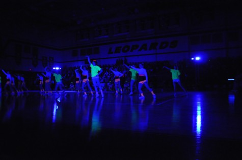 Cheerleaders light up the room while they perform their routine during the Black Light Pep Rally Friday, April 11, 2014.