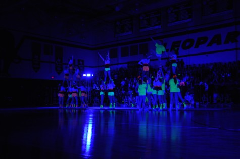 Cheerleaders perform the stunting part of their routine during the Black Light Pep Rally Friday, April 11, 2014.
