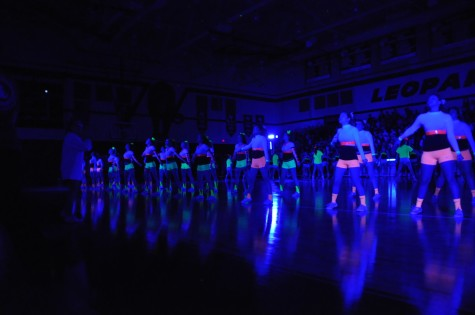 Cheerleaders perform the cowbell dance during the Black Light Pep Rally Friday, April 11, 2014.